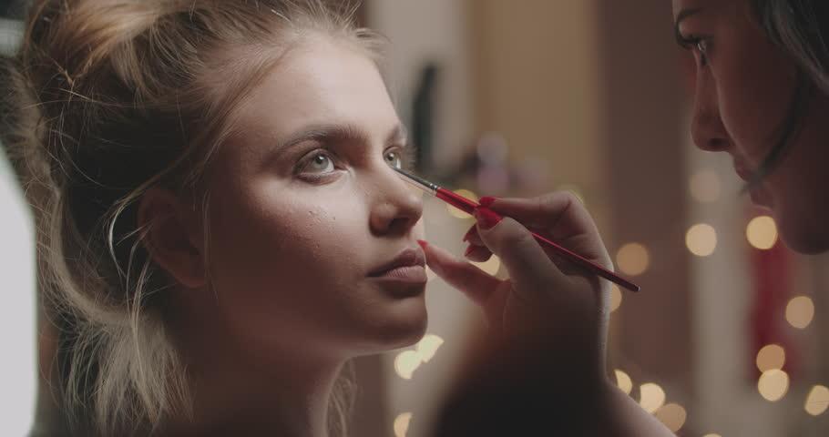 professional makeup artist making eye-makeup for young model 4k