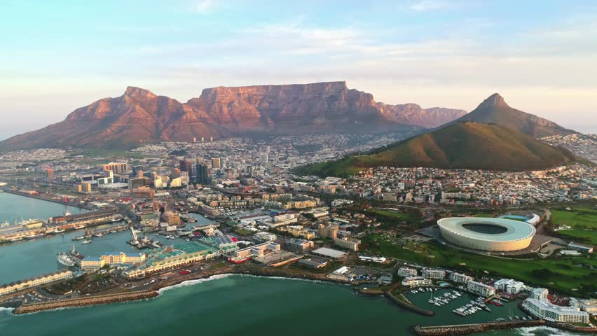 Aerial view flying towards the city of Cape Town with Table Mountain as a backdrop Royalty-Free Stock Footage #1013687999