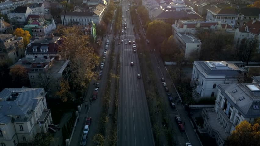 Arial shot flying down a busy Budapest street with sun-flares and vibrant Autumn colors featuring mid century architecture. | Shutterstock HD Video #1013698664