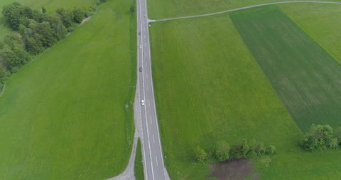 Flying above of highway with cars through green meadows, drone view
