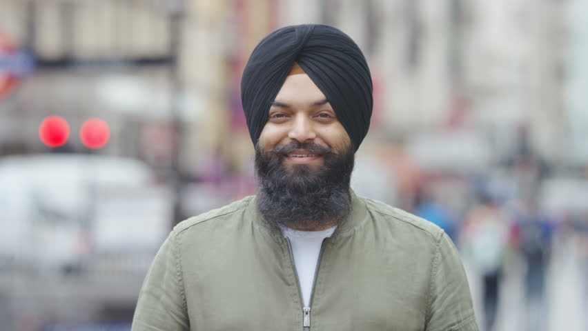 Portrait of young Indian male wearing a turban and smiling to camera, in slow motion | Shutterstock HD Video #1013709617