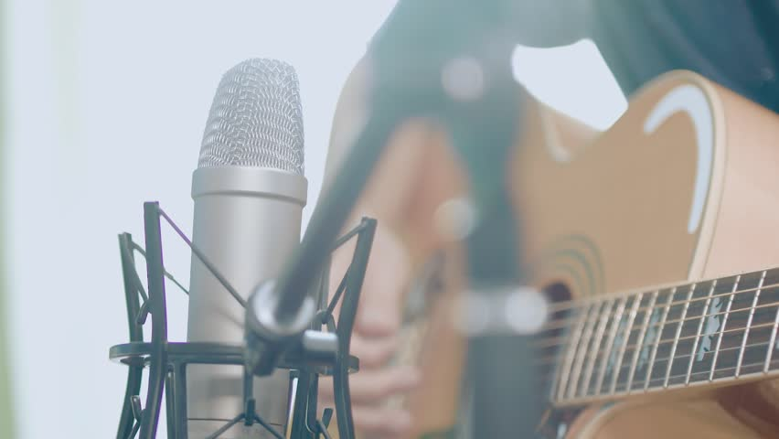 Closeup of a guy playing the acoustic guitar with a recording microphone in front of him