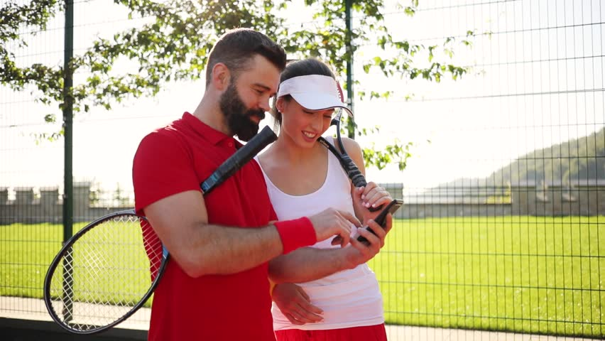 Cheerful tennis players actively using smartphone and laughing on tennis court in a bright sunlight. Having fun, surfing the internet, memes, funny compilations. Royalty-Free Stock Footage #1013715158