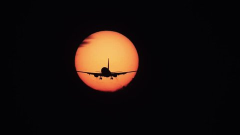 Silhouette of jumbo jet plane with landing gear and big sun in the background, high contrast uhd version