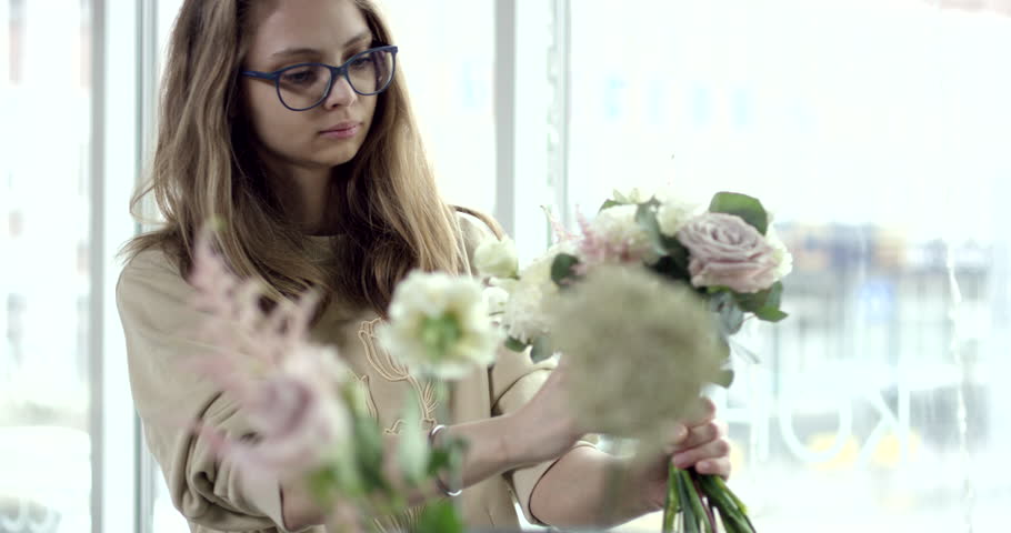 Young Florist Assembles a Rustic Wedding Bouquet. Young florist assembles a perfect wedding bouquet. Her flowers are wonderful, the colors are so rustic, she has perfect taste. #1013727026