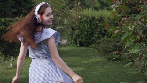 Young woman with headphones listening music and walking in the summer park.
