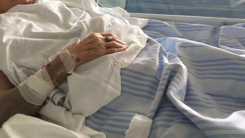 Hand of an Elderly patient sleeping on a medical bed in hospital room