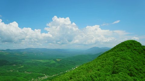 Beautiful landscape in green mountains. Blue sky with running clouds. Summer view in the morning or afternoon. 4K video