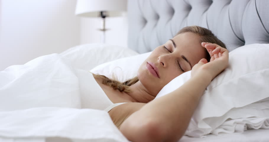 Beautiful lifestyle woman waking up in bed at home RED DRAGON