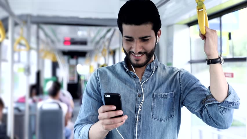 Close up view of Handsome Man Standing on the Public Transport. Interior of Crowded Tram. Man Types on his Mobile Phone. Listening to Music with his Headphones. Luxurious Wristwatch. Casual Clothing.