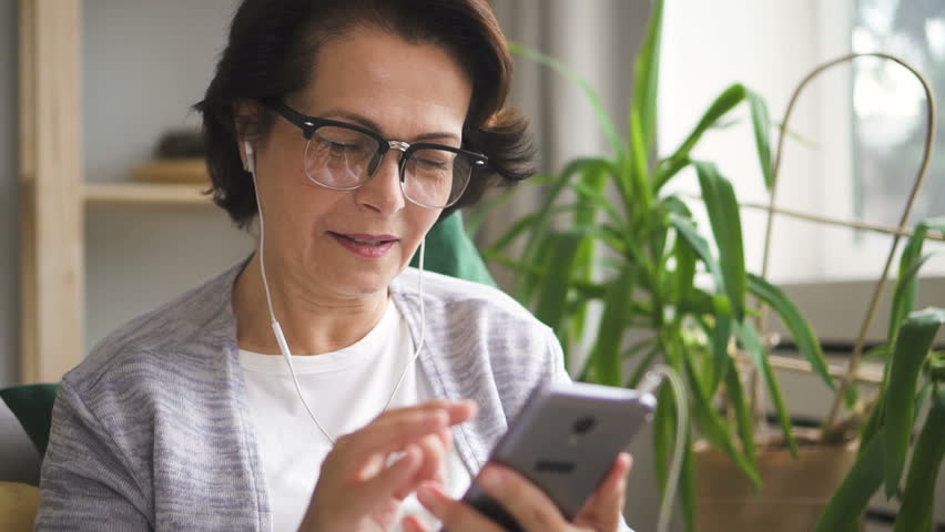 Mature woman in glasses and earphones scrolling screen of her smartphone to choose music, being at home with plants on the background. Portrait. Indoors. | Shutterstock HD Video #1013757122