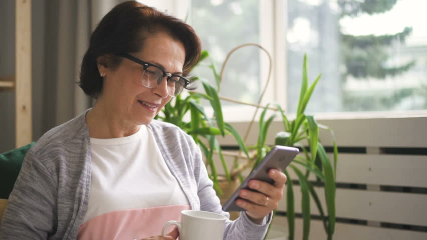 Happy senior woman is using smartphone sitting on sofa at home, attractive lady in eyeglasses is looking at gadget screen, holding mug in hand, smiling in room with window and green plants. Concept | Shutterstock HD Video #1013757239