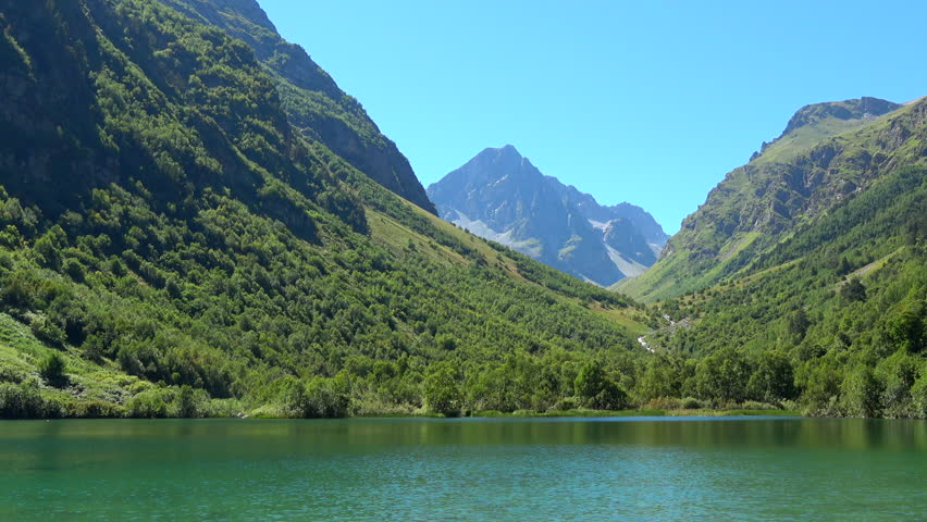 View lake scenes in mountains, national park Dombai, Caucasus, Russia, Europe. Summer landscape, sunshine weather, blue sky and sunny day. 4K footage, video camera format 3840x2160   Shutterstock HD Video #1013761859