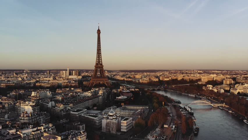 Aerial shot of Paris with the Eiffel tower and the Seine in the center. The surrounding buildings are painted in orange light by the rising sun. | Shutterstock HD Video #1013776085