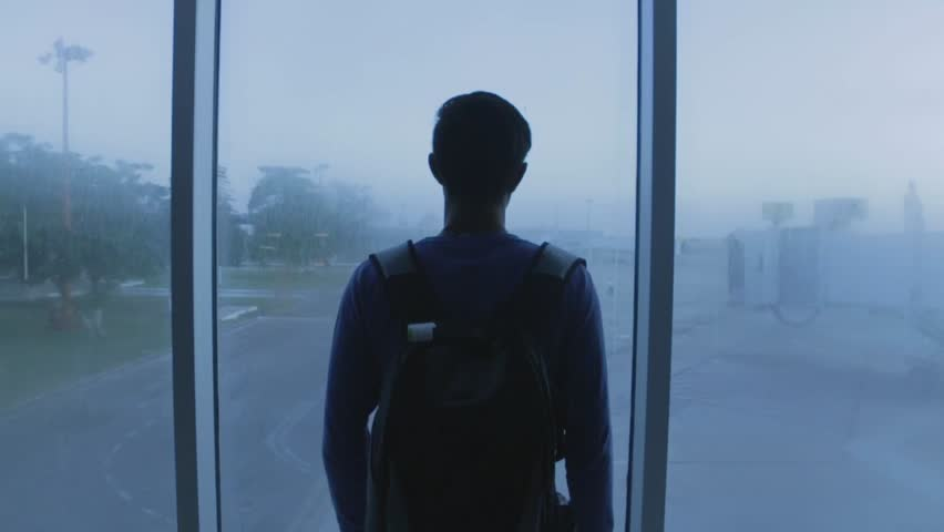 Dramatic shot of a young man looking out an airport window #1013785286