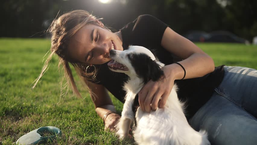 Smiling lady taking free time with her dog. Woman relaxing in the nature with her little dog. Scratching her back. Dog licking her owner nose. Close up | Shutterstock HD Video #1013793116