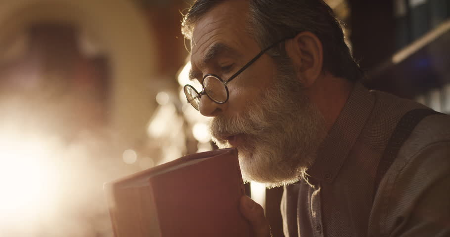 Close up of the old gray haired man in glasses blowing a dust from a book in the library before reading it. | Shutterstock HD Video #1013806382