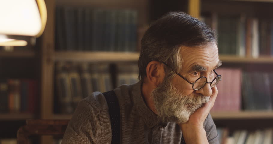 Portrait of the senior man in glasses sitting in the library and thinking while leaning on his hand.   Shutterstock HD Video #1013806457