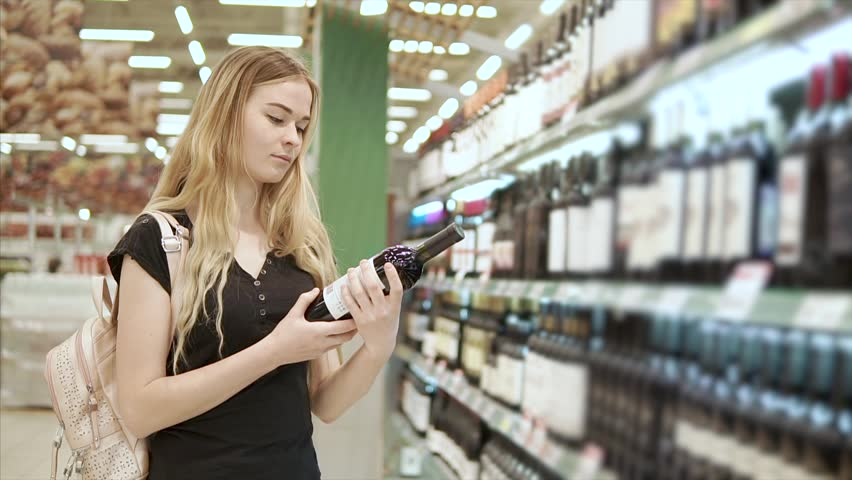 Alone girl is examining a label of a bottle with red wine in shop. She is standing in front of big shelves with alcohol beverages #1013807402