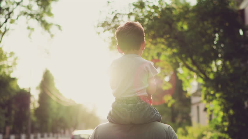 Father and son walking in city at sunset. Two year old kid is sitting on the parent's shoulders. Happy family concept #1013812409