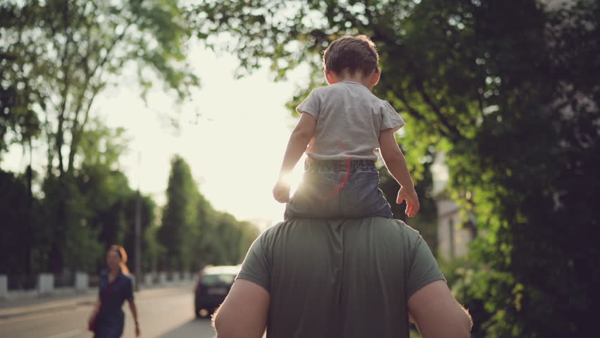 Father and son walking in city at sunset. Two year old kid is sitting on the parent's shoulders. Happy family concept. Footage in slow motion #1013812835
