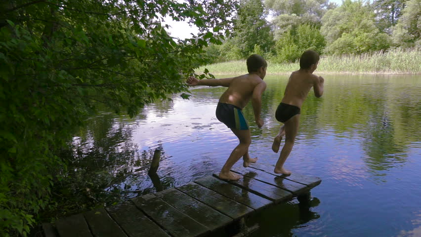 Two boys jump together from pier to the river in the forest, slow motion #1013821433
