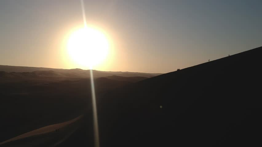 Aerial drone footage of a sunset above the sand dunes of Peru. Close to Ica and Huacachina oasis. Boogie cars driving and people sandboarding.   Shutterstock HD Video #1013831117