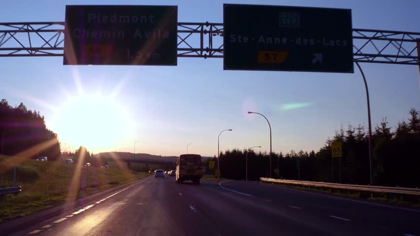 Overtaking a schoolbus under a viaduct while driving on the highway with perfect blue sky at sunset