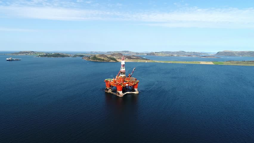 Aerial footage of Oil and Gas Drilling rigs POI shot of a semi submersible and a jackup the background hot stacked in a bay.