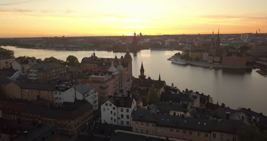 Aerial view of Stockholm Sweden during the golden hour. The dronees forward flying close to a tower. Majestic colours in the sky.