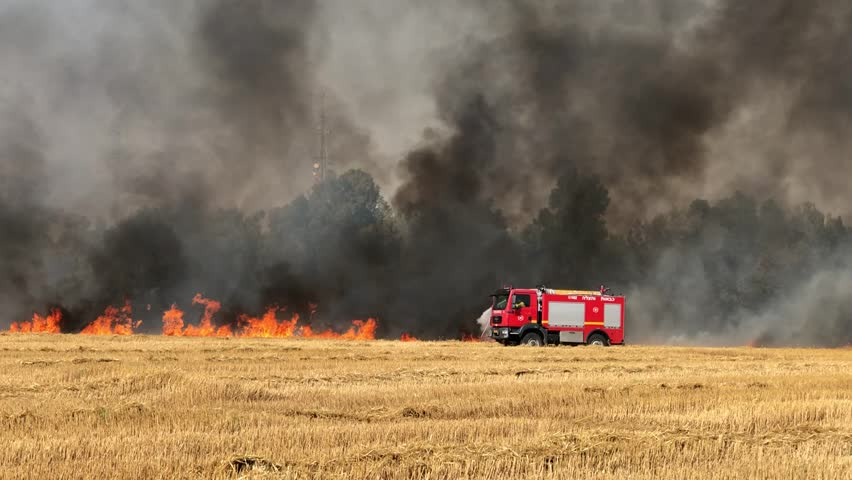 Fire engine turns off the fire in a wheat field. Fires in Israel that caused from burning kites and balloons that sent from the Gaza strip. 18.05.2018 in Nahal Oz fields, Israel.