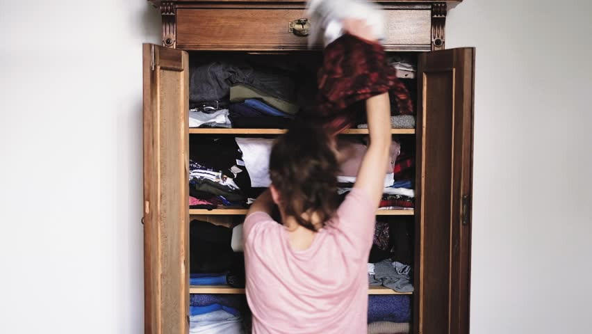 Angry young woman is throwing clothes from old retro vintage wooden wardrobe and after unsuccessful clothes search, view from back, slow motion 1920p HD | Shutterstock HD Video #1013848754