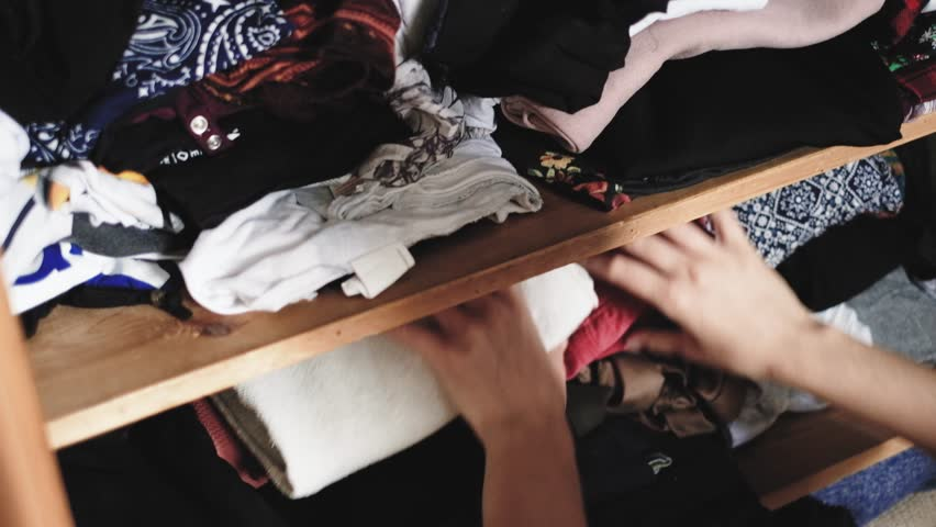 Young woman is looking for clothes, searching at home, in old vintage retro wooden wardrobe, handheld shot in 4K UHD | Shutterstock HD Video #1013848763
