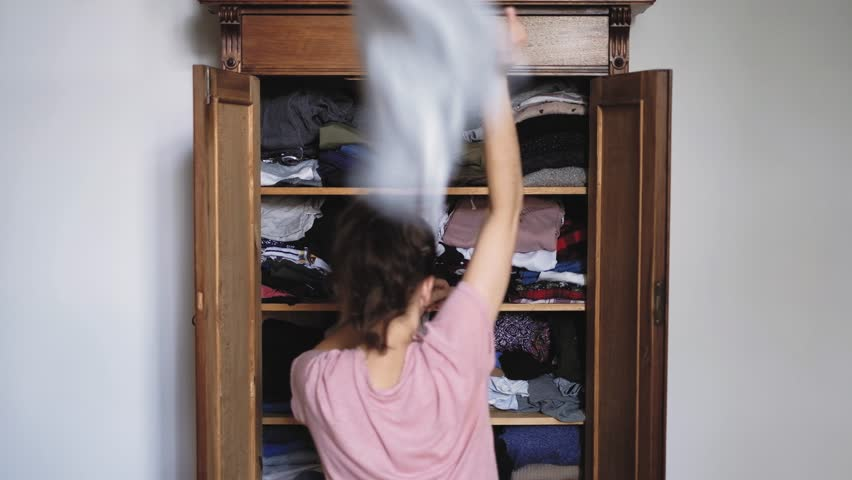 Angry young woman is throwing clothes from old retro vintage wooden wardrobe and after unsuccessful clothes search, view from back, shot in 4K UHD | Shutterstock HD Video #1013848769