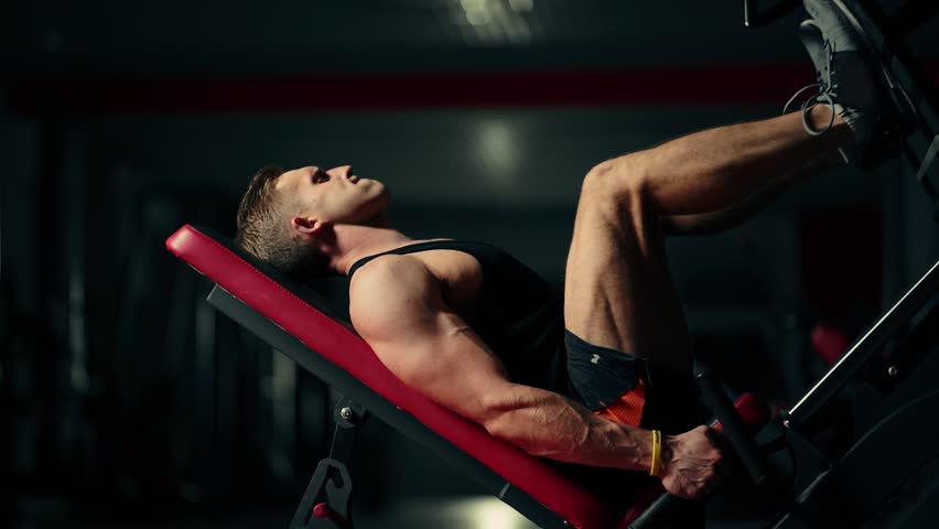 A muscular man performs exercises on a sports training apparatus for leg muscles in a dark gym, lifting weights