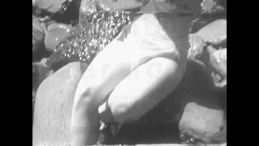 CIRCA 1950s - Pin-up girl Adele Dolman tries to sit on the rocks of a beach while the waves come in, but her bikini top slips a few times.
