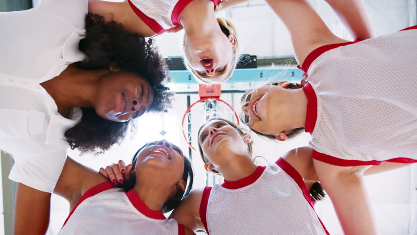 Low Angle View Of Female High School Basketball Players Having Team Talk With Coach