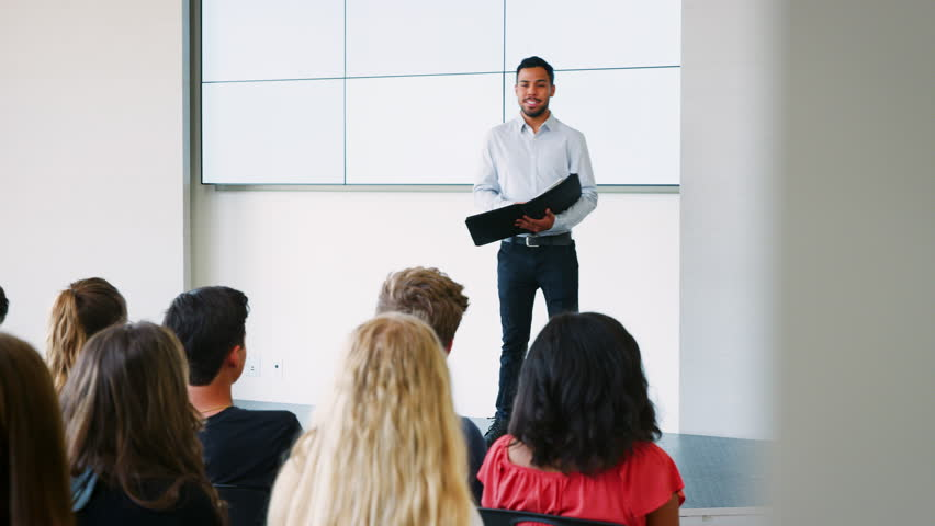 Teacher Giving Presentation To High School Class In Front Of Screen #1013868263