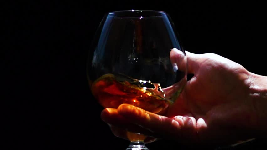 Man's hand stir slowly cognac in the glass, slow motion. black background