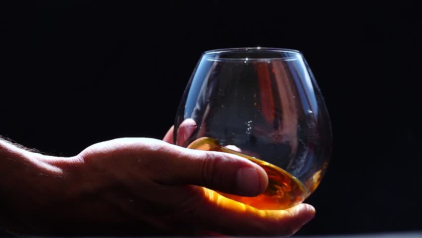Man   holding, swirling cognac, slow motion shot, black background