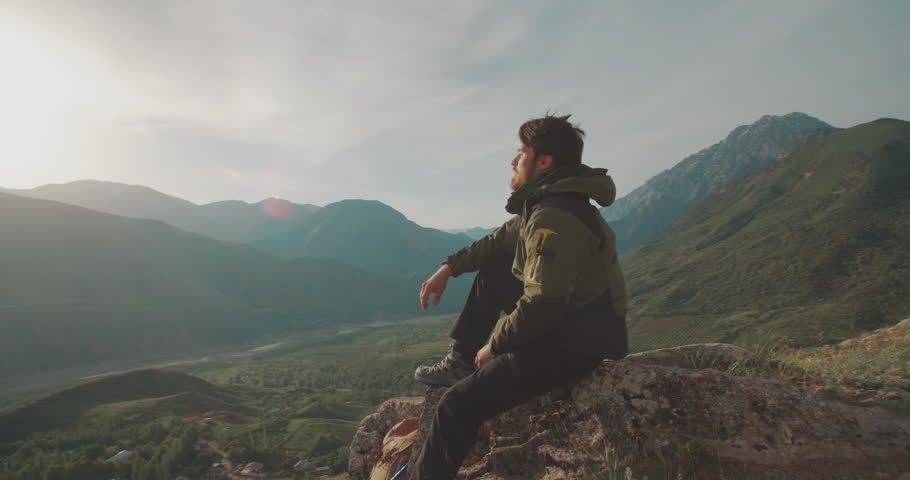 Lonesome climber sitting on top of mountain. Adventurer in expedition. Freedom, zen concept 4k | Shutterstock HD Video #1013875208