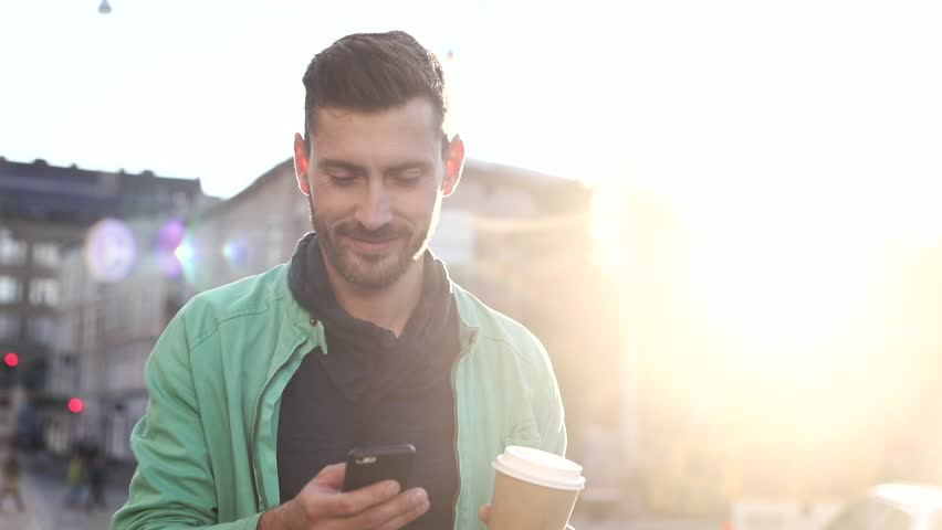 Handsome Bearded Man Walking in the Wide Street at Sunset. Drinking Coffee to go. Using his Mobile Phone. Enjoying the Evening Walk. Man Walking in the Crowded Street full of Cars.