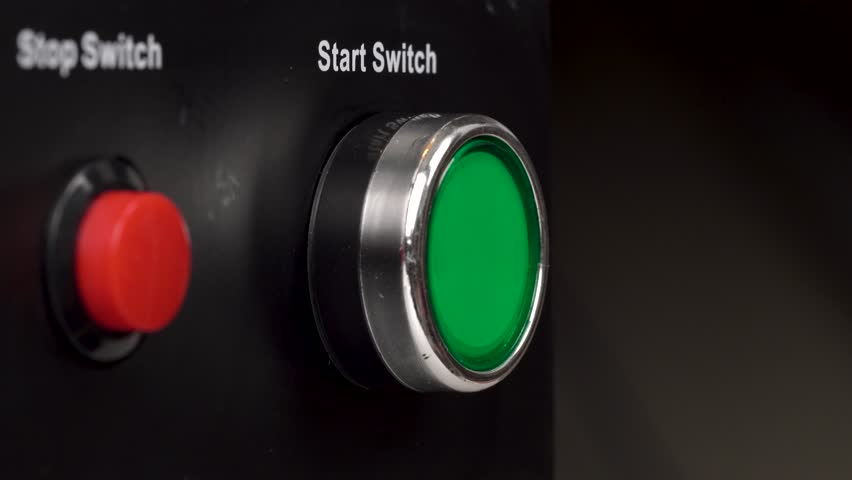 Closeup of two buttons in the frame. Green start switch and red stop switch buttons. Finger press the green start switch button.