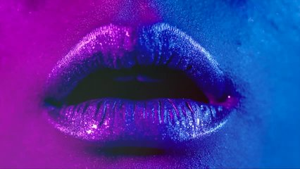 Lips kiss in neon UV lights. Beauty sexy model lips close-up, disco. Woman mouth closeup. Metallic lipstick. Purple and blue ultraviolet lights. Slow motion 4K UHD video