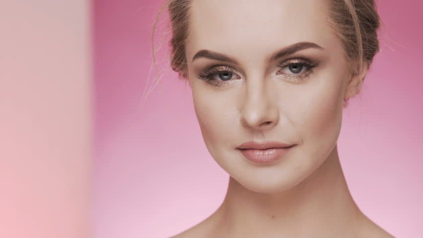 Beauty video concept, close up portrait at pink background, smiling and looking at camera