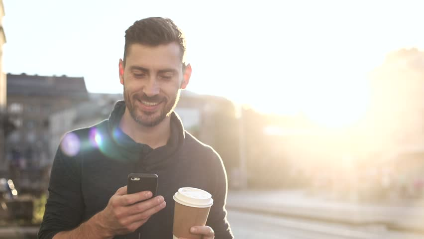 Happily Smiling Attractive Man Walking down the Street. Typing on his Smartphone with Interest. Enjoying the Evening Walk. Drinking Delicious Coffe. Crowded City on the Background. | Shutterstock HD Video #1013880362