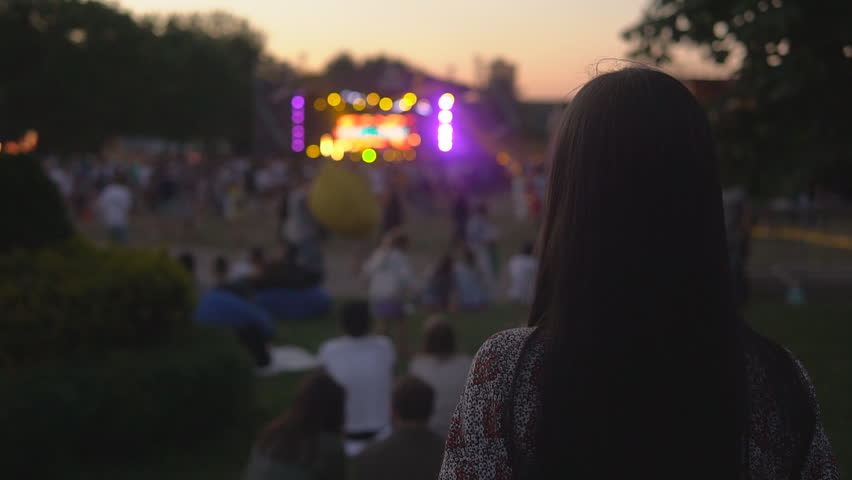 Back view of young brunette woman with long hair on festival at the evening   Shutterstock HD Video #1013893463