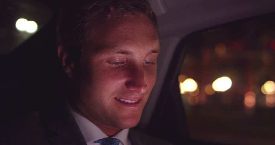 Close up of young businessman sitting in backseat of car looking out window smiling and texting #1013897432