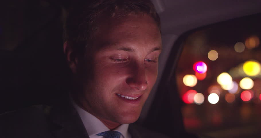 Close up of young businessman sitting in backseat of car looking out window smiling and texting #1013897435