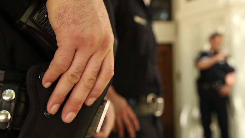Close-up shot of a cop's hand resting on his holstered gun as he stands around at a crime scene with other cops. Detectives walk by in the background.